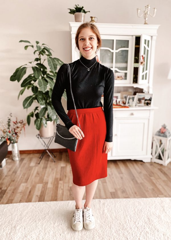 Girl wearing dark sweater, red skirt and sneakers