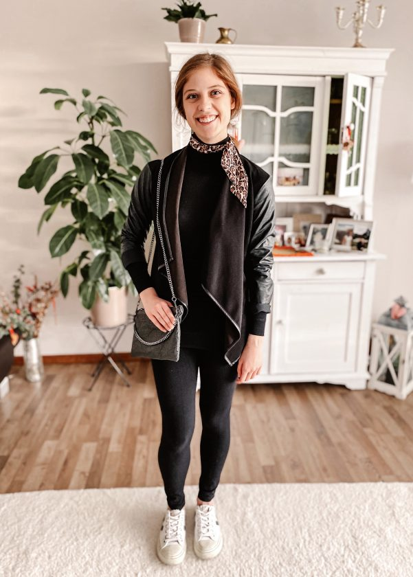 Girl wearing dark sweater, jacket and leggings with white sneakers