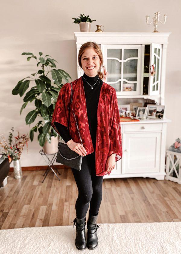 Girl wearing secondhand black sweater, red jacket and dark leggings