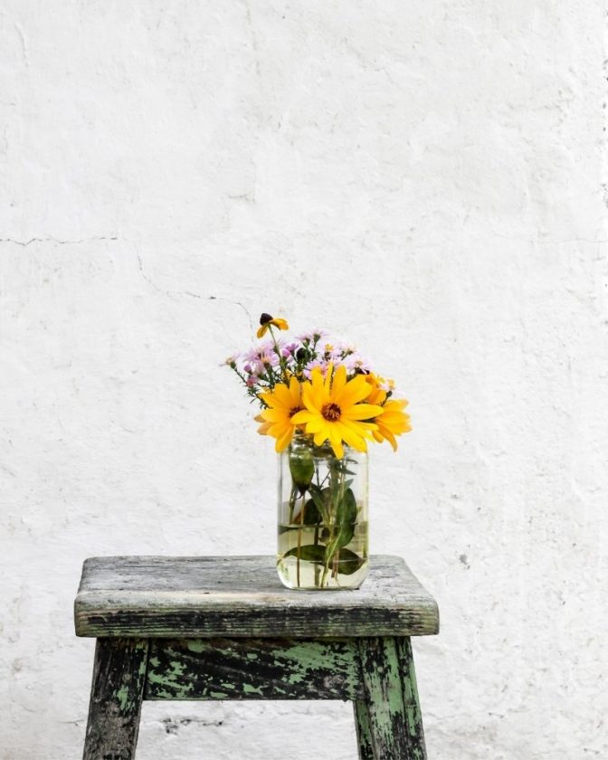 Minimalist image of a stool and flowers